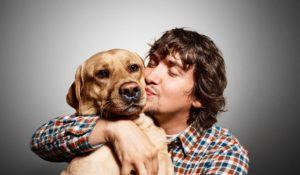 Closeup portrait handsome young hipster man, kissing his good friend dog isolated black grey background. Positive human emotions, facial expression, feelings.